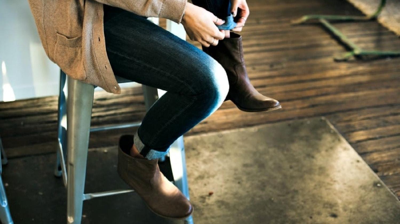 Mujer sentada en un taburete para enrollar sus jeans sobre un par de botines de cuero