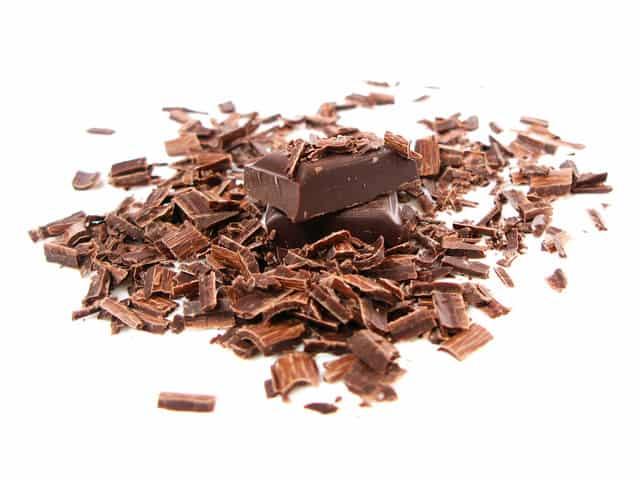 Barra de chocolate rallado sobre un fondo blanco.