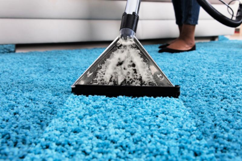 Mujer limpieza a vapor alfombra de pelusa turquesa con máquina