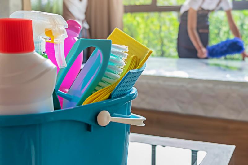 Cubo de productos de limpieza en el mostrador con mujer desempolvando en el fondo