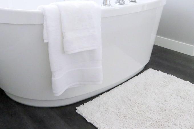 Cómo lavar alfombras de baño: alfombra blanca frente a una bañera