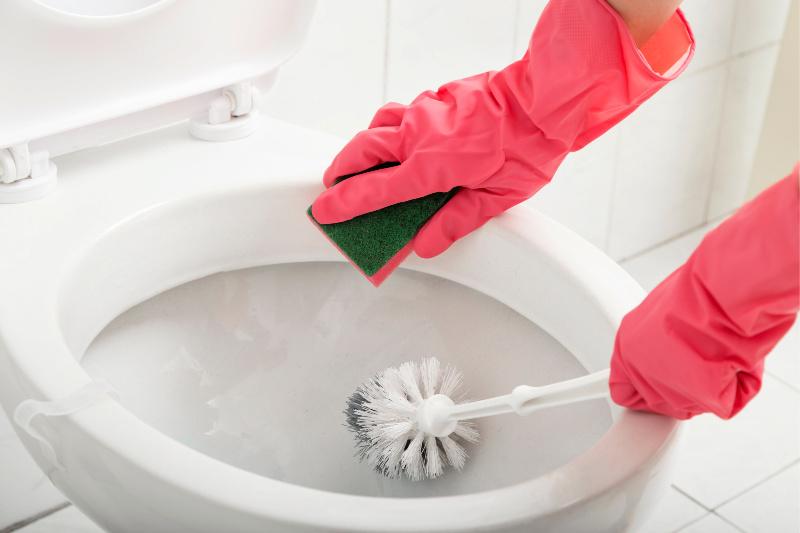 Mujer fregar el inodoro con una esponja y un cepillo para limpiar profundamente un baño