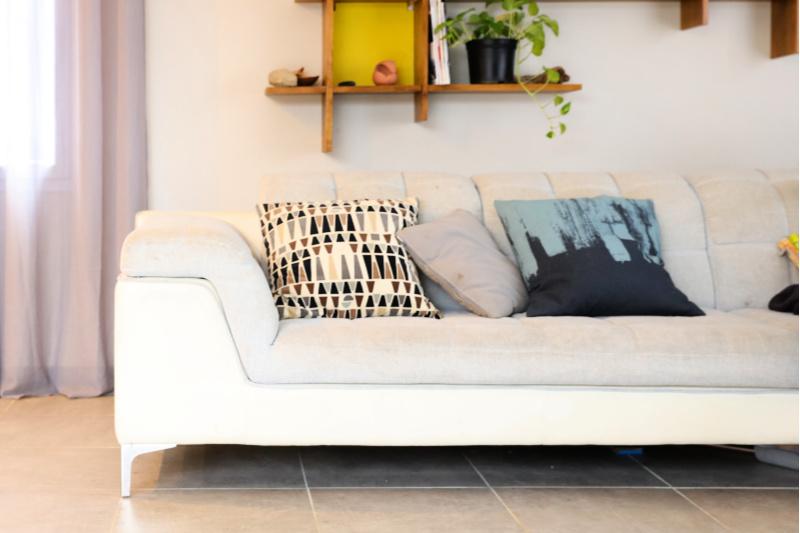Sala de estar moderna con cojines en un sofá blanco y estantes organizados en la pared