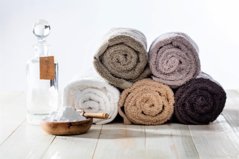 Toallas enrolladas en tonos tierra junto a un tazón de bicarbonato de sodio y una botella de vinagre para lavar la ropa