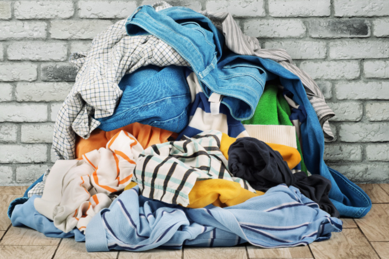 Montón de ropa sucia sin clasificar sobre un piso de madera