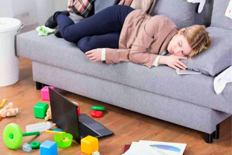 Mujer en el sofá rodeada de desorden que necesita encontrar motivación para limpiar