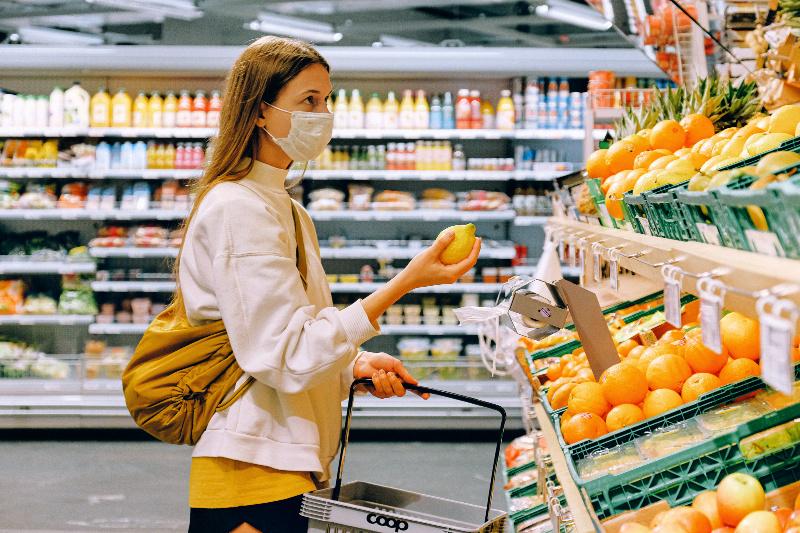 Mujer vistiendo máscara de tela en la tienda de comestibles