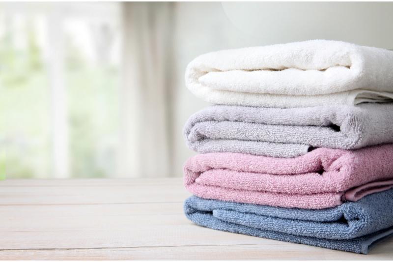 Pila de toallas cuidadosamente dobladas sobre una mesa de madera delante de una ventana