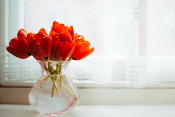 Flores en un jarrón de vidrio en el alféizar de una ventana con cortinas transparentes en el fondo que muestran cómo limpiar cortinas