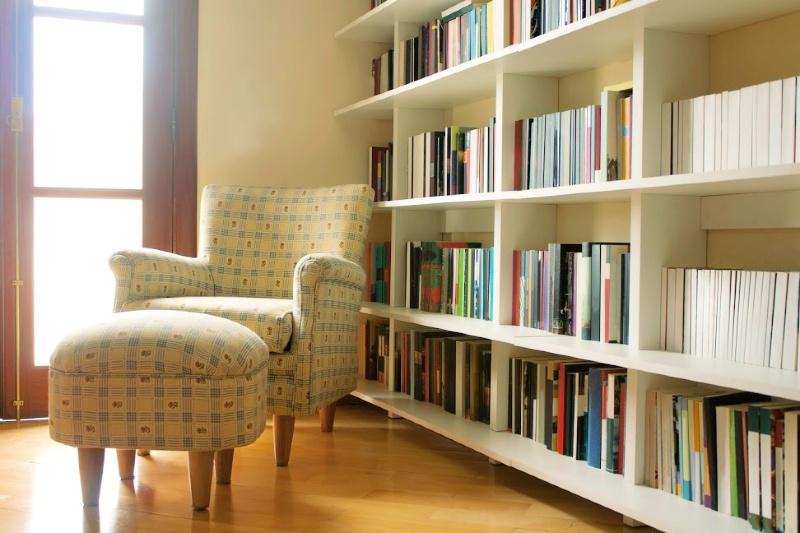 Cómoda silla y otomana junto a las estanterías de la biblioteca en casa
