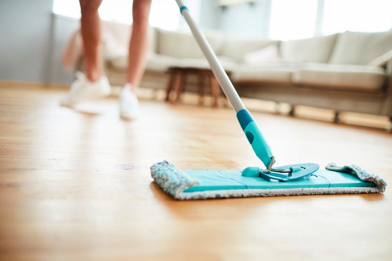 Mujer demostrando cómo limpiar pisos de madera con un trapeador de microfibra seco
