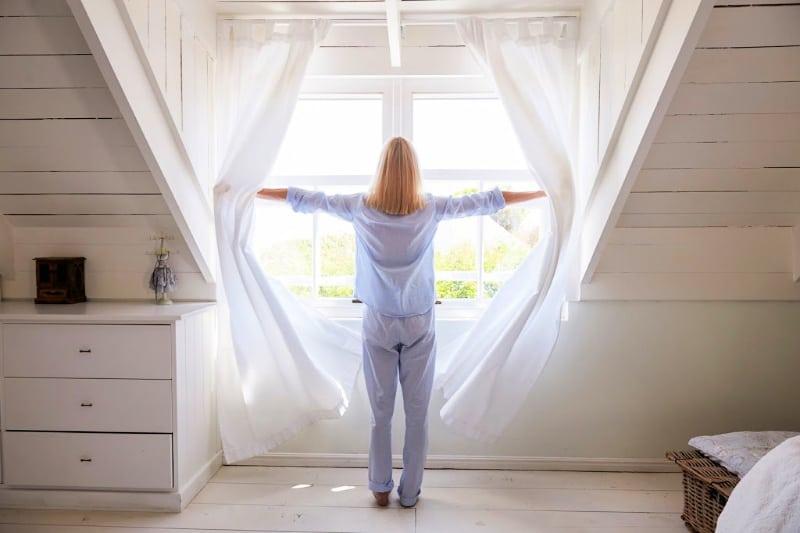 Mujer abriendo cortinas para mejorar el aire interior