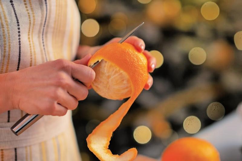 Mujer usando un cuchillo para pelar una naranja fresca para demostrar cómo reutilizar los restos de cocina