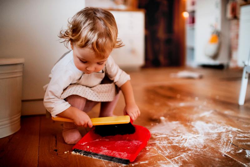Niña pequeña en un vestido con un recogedor y una escoba de mano para limpiar la harina derramada en el piso