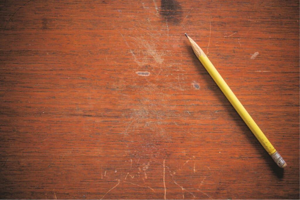 Un lápiz se encuentra junto a rasguños leves y profundos en una mesa de madera esperando ser reparado