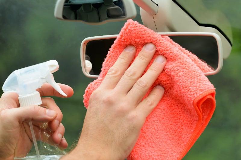 Limpieza del interior del automóvil con atomizador y paño de microfibra para limpiar el espejo retrovisor
