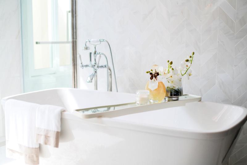Tina independiente de porcelana blanca con grifos cromados y accesorios de baño de vidrio
