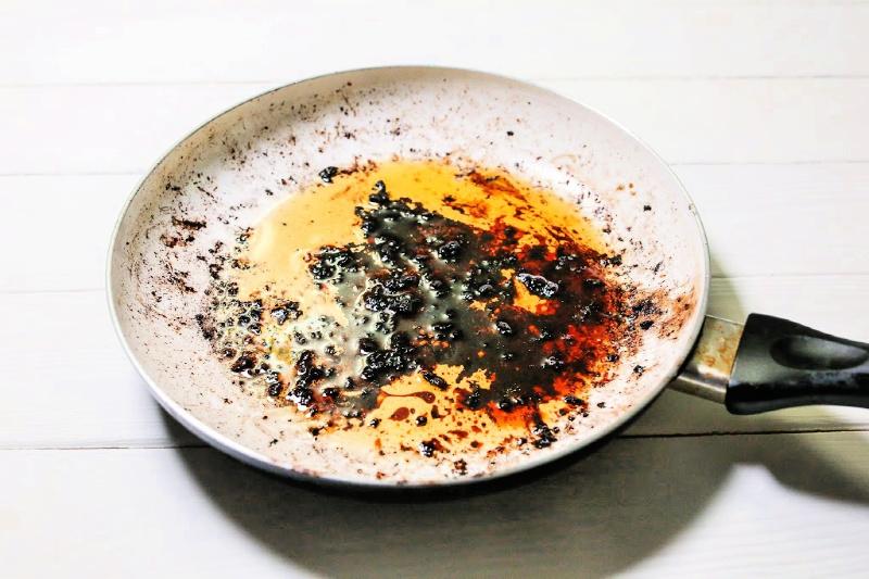 Sobre la cabeza de los alimentos quemados en la sartén que deben limpiarse