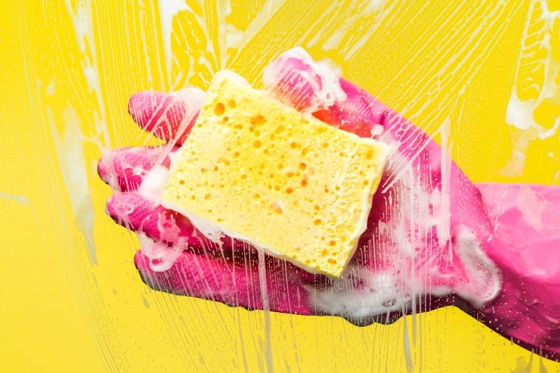 Mano en un guante de goma sosteniendo una esponja con un removedor de espuma de jabón casero que no se frota