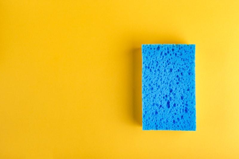 Esponja de cocina azul sobre fondo amarillo