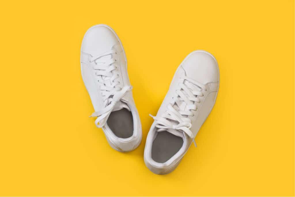 Zapatillas de tenis de cuero blanco sobre un fondo amarillo